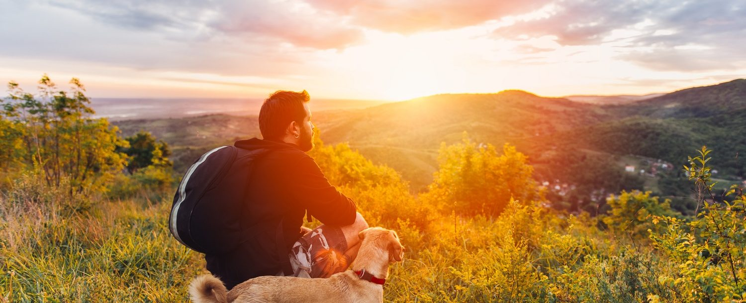 man with dog hiking looking at the sunset